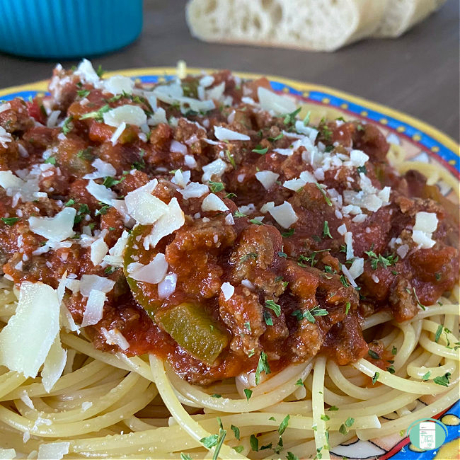 close up of noodles topped with red sauce and Parmesan cheese