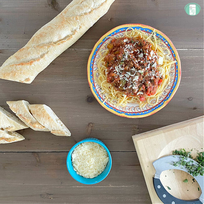 sliced French bread, bowl of grated white cheese, plate of spaghetti, and board with chopped herbs