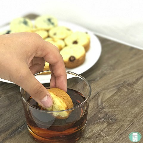 close up of someone dipping pancake mini muffins into syrup