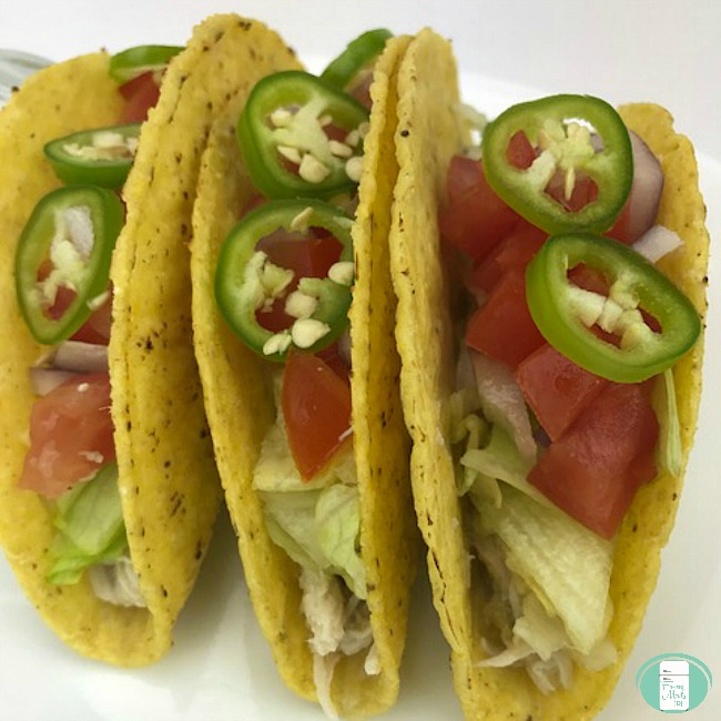 close up of chicken tacos with lettuce, tomato and slices of jalapeno