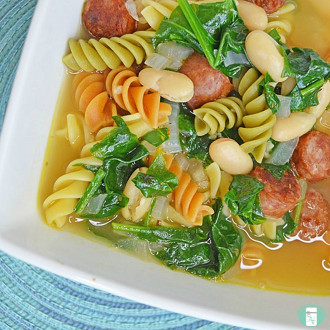 close up of spinach and sausage white bean soup with colored pasta