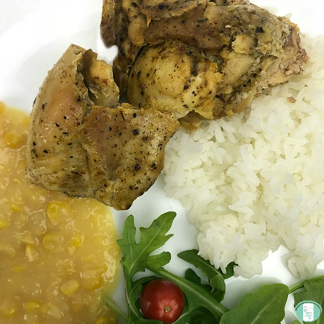 close up of lemon mustard chicken with sides of salad, rice and creamed corn