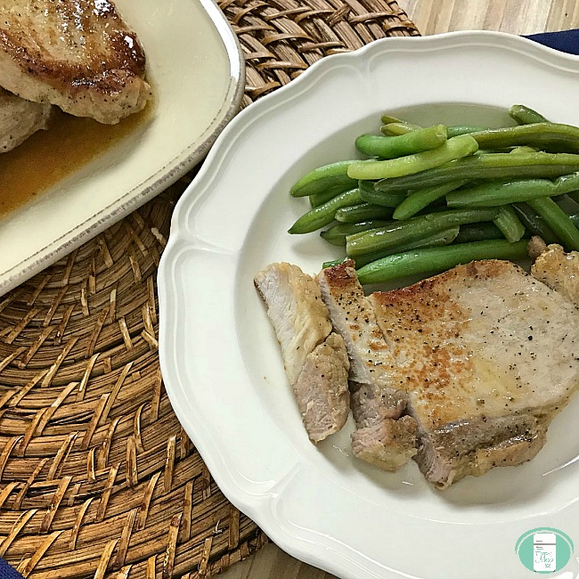close up of simple marinated pork chops with green beans on the side
