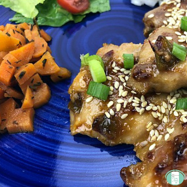 close up of honey sesame chicken rice with honey maple carrots