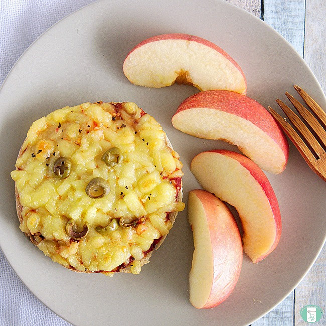 close up of English muffin pizza with apples on the side