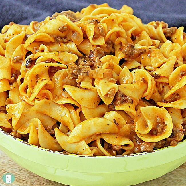 close up of creamy tomato beef skillet meal in a bowl with lots of pasta