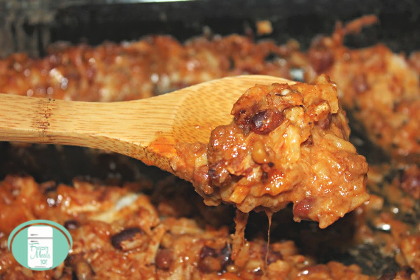 close up of a wooden spoon lifting some chili hash brown casserole from a crockpot