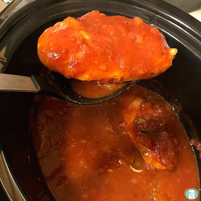 a spoon is lifting chicken cacciatore from a crock pot