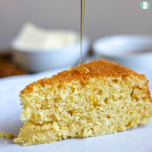 close up of old-fashioned southern corn bread with syrup being poured on it