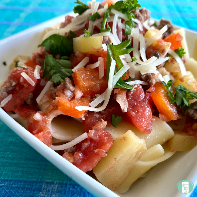 Ragu with tomatoes, beef and sausage served on pasta with cheese and parsley on top