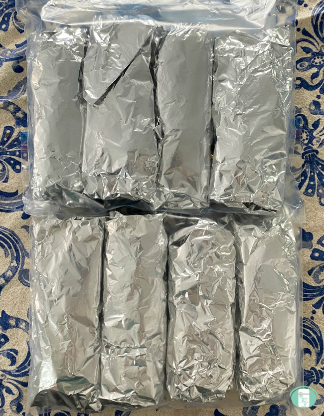 beef and bean burritos wrapped in foil and in a freezer bag
