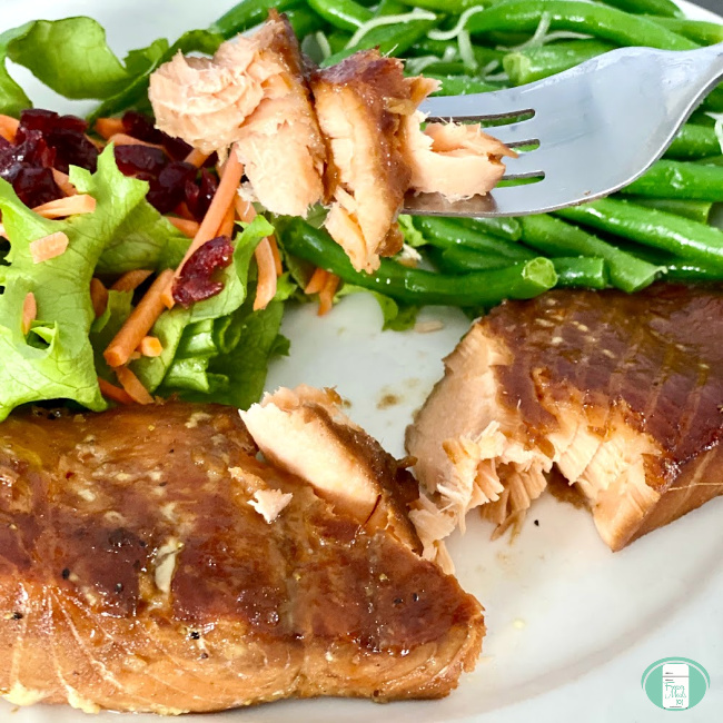 close up of ginger soy salmon being lifted by a fork with salad and green beans on the side
