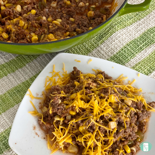 pot and plate with southern-style ground beef casserole with cheese on top