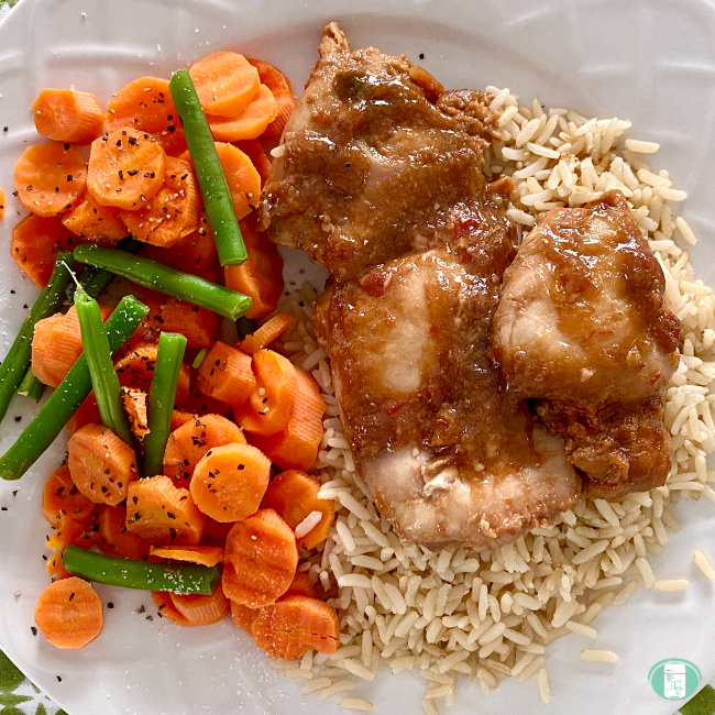 close up of gingery salsa chicken on a bed of rice with carrots and green beans