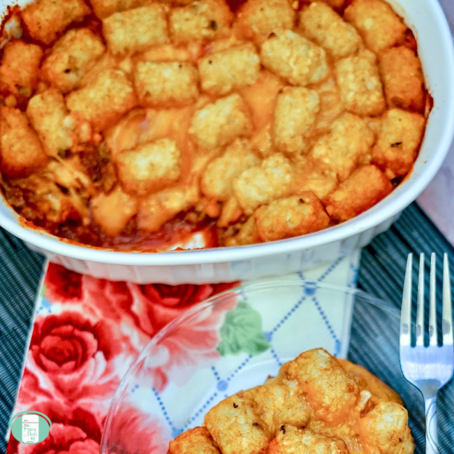 close up of casserole dish with tater tot sloppy joes and a plate with some on it ready to serve