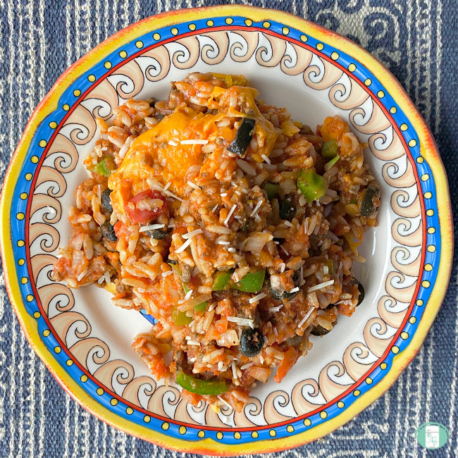 close up of Spanish rice casserole on a plate, topped with cheese