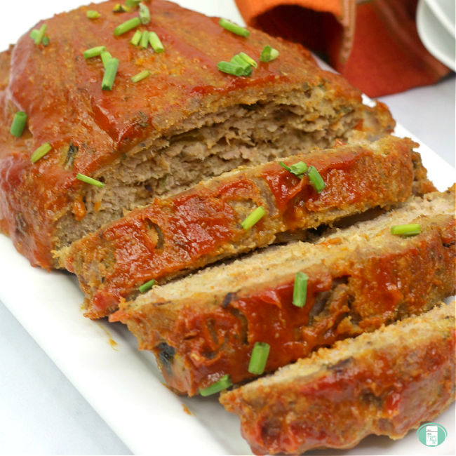sliced turkey meatloaf topped with sliced green onions on a white plate