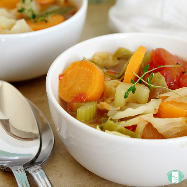 white bowl of soup with chunky vegetables next to two spoons