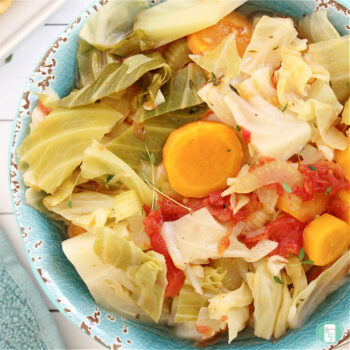 blue bowl heaped with vegetables like carrots, cabbage, tomatoes