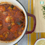 pot holding red sauce and chunks of chicken and vegetables