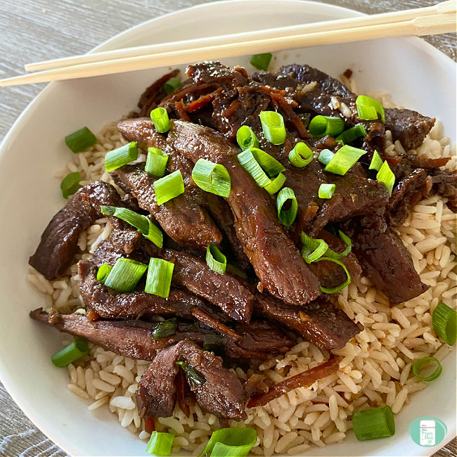 white bowl filled with rice topped with Mongolian beef strips and sliced green onions. Chopsticks rest of top.