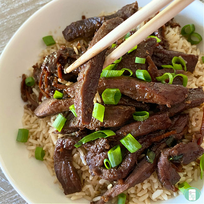 white bowl with rice, Mongolian beef strips, green onions, and chopsticks