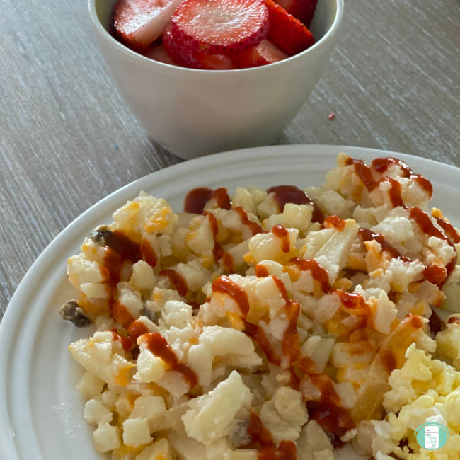 plate of hash browns topped with ketchup. A bowl of strawberries are nearby.