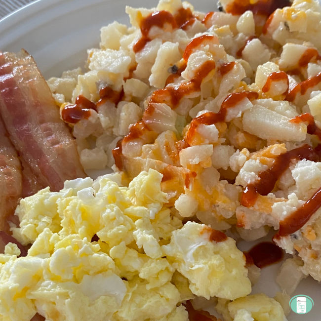 plate of bacon, scrambled eggs, and ketchup topped hash browns