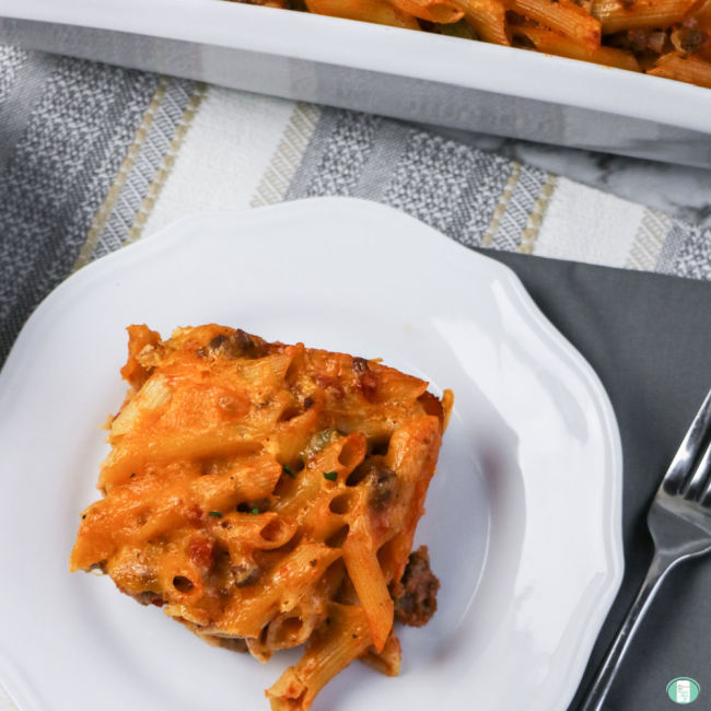 square piece of pasta bake on a white plate next to a fork