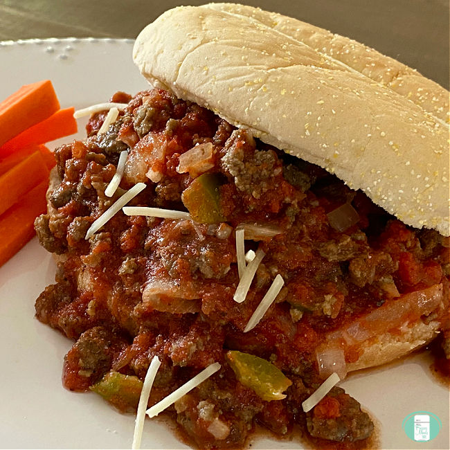 bun filled with sloppy joes mixture on a plate next to carrots