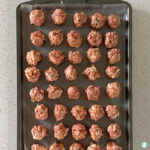 raw meatballs on a cookie sheet