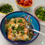 blue bowl with fork in cheesy breakfast casserole with other bowls of ingredients behind