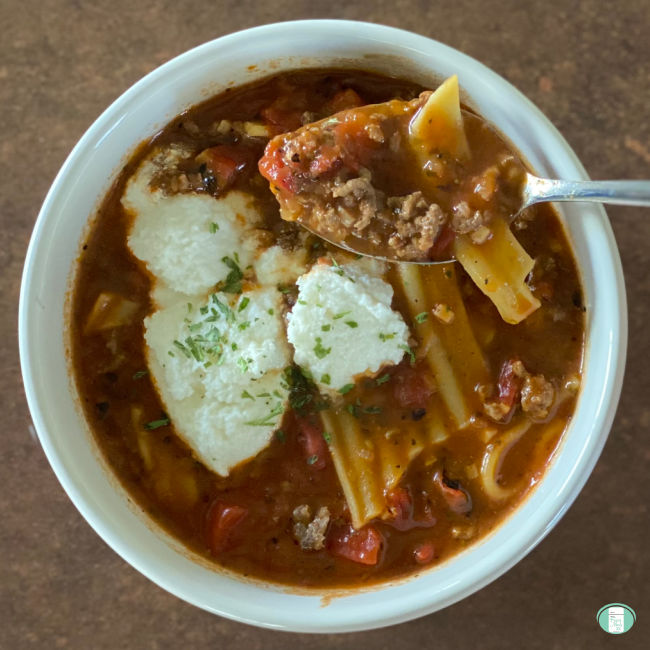 bowl of lasagna soup with a spoon lifting a scoop out