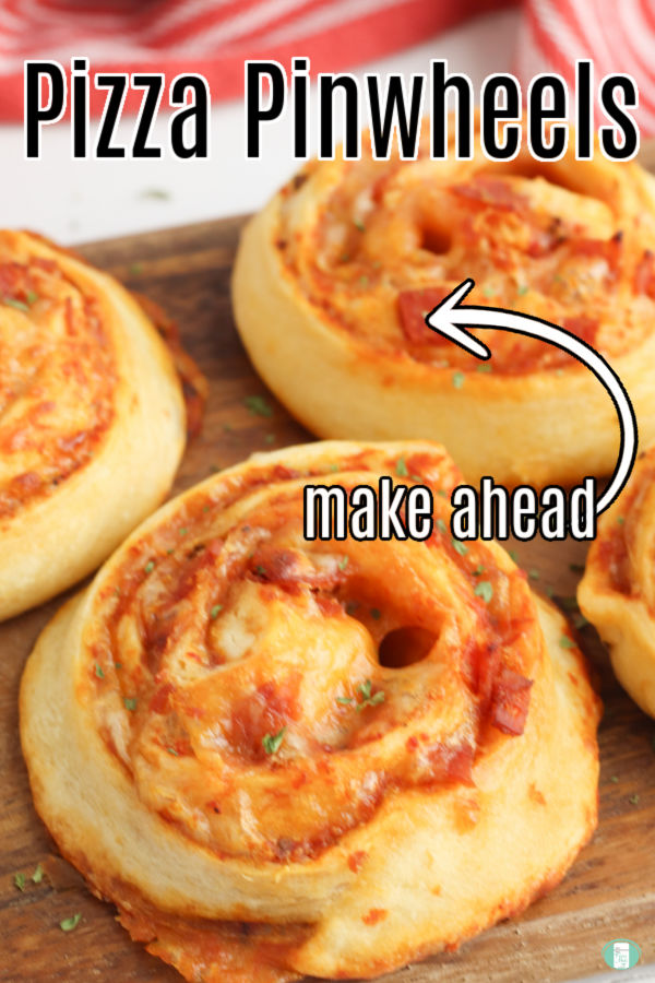 baked pizza pinwheels are shown on a wooden board with a red tea towel in the background